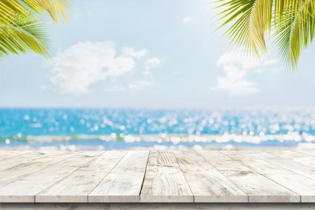 Parte superiore della tabella di legno con vista sul mare e foglie di palma, luce del bokeh della sfuocatura del mare calmo e cielo alla spiaggia tropicale Foto Premium