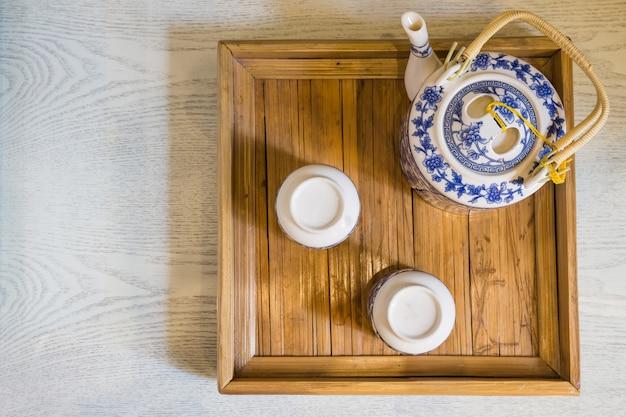 Parte superiore della tazza bianca tradizionale di tè e teiera in primo piano di legno del vassoio sulla tavola Foto Premium