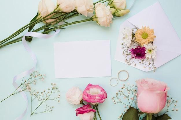 Partecipazione di nozze in bianco con due anelli e decorazione floreale su sfondo blu Foto Gratuite