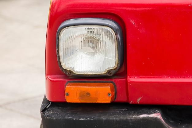 Parti della lampada davanti all'automobile rossa dell'annata Foto Premium