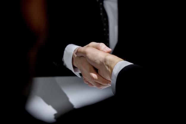 Partner commerciali facendo stretta di mano in ombra scura Foto Premium