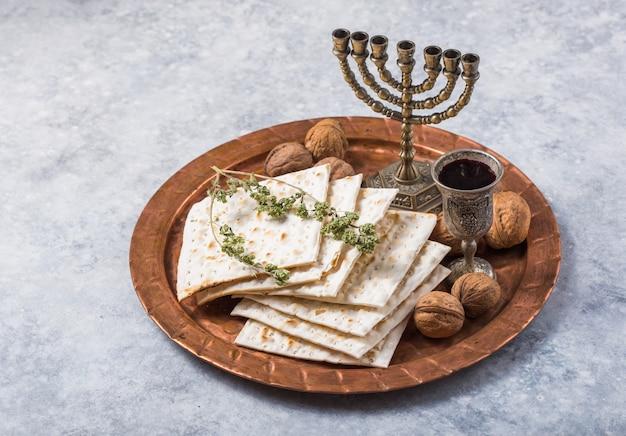 Pasqua ebraica, la festa del pane azzimo, pane matzah e bicchieri di vino rosso sul vassoio di metallo rotondo lucido. Foto Premium