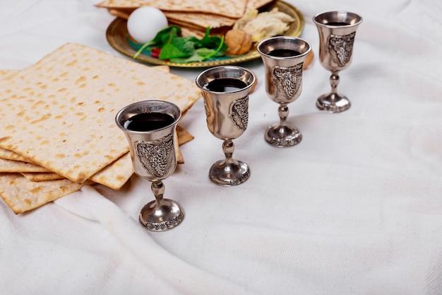 Pasqua ebraica pane azzimo vacanza pane, quattro bicchieri vino kosher sul tavolo di legno. Foto Premium