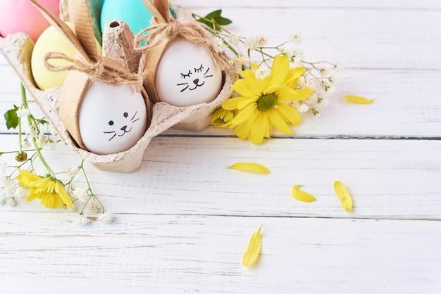 Pasqua ha colorato le uova con i fronti dipinti in vassoio con decorationd su un fondo bianco Foto Premium