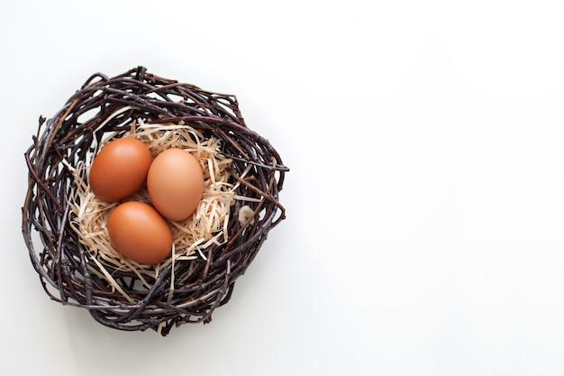 Pasqua! uova di gallina in un nido con rami, agricoltura. uova di pasqua sul tavolo nel nido. Foto Premium