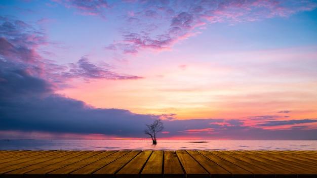Passaggio pedonale di legno con l'albero solo in lago e cielo variopinto al villaggio di pak pra, pha Foto Premium