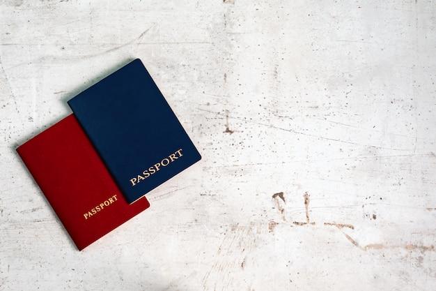 Passaporti di due viaggiatori rossi e blu. concetto di viaggio. Foto Premium