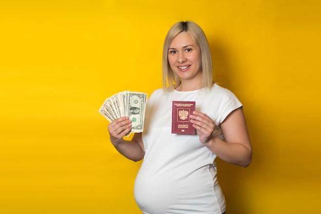 Passaporto della tenuta della donna incinta con soldi. vantaggi per le donne in gravidanza, sul muro giallo Foto Premium