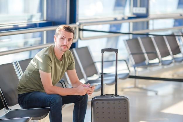 Passeggero in un salotto dell'aeroporto in attesa di volo aereo Foto Premium