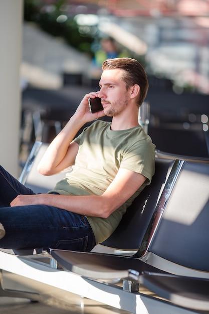 Passeggero in una sala dell'aeroporto in attesa di volo aereo, giovane uomo con cellulare in aeroporto in attesa di atterraggio Foto Premium