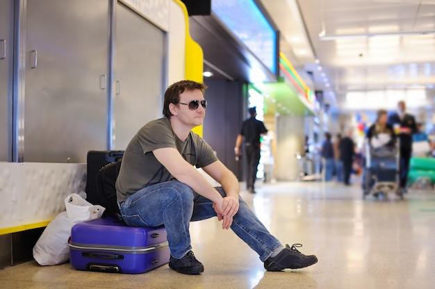 Passeggero maschio stanco all'aeroporto che si siede sulle valigie Foto Premium