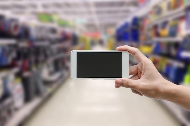 Passi a tenuta lo smart phone mobile con lo schermo di monitor in bianco sulla sfuocatura del supermercato, concetto di affari Foto Premium