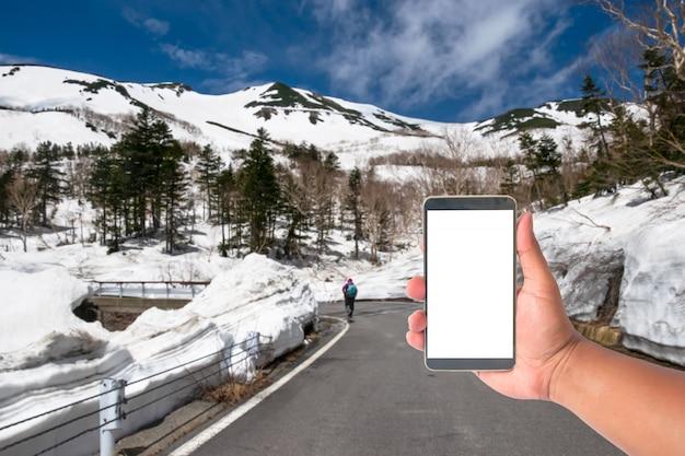 Passi il telefono cellulare della tenuta con una strada della montagna delle alpi del giappone della parete della neve, giappone. Foto Premium