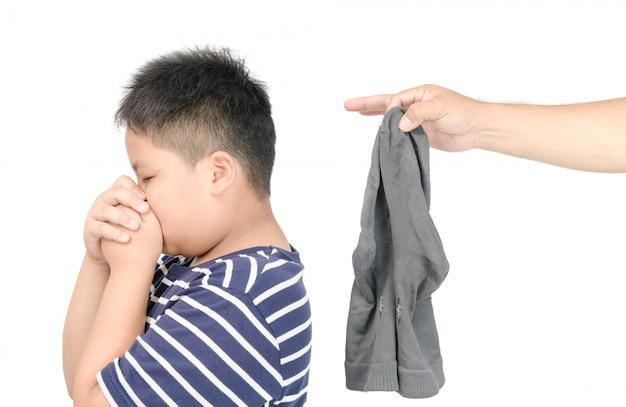 Passi l'uomo che tiene i calzini puzzolenti sporchi isolati su fondo bianco, concetto sgradevole dell'odore Foto Premium