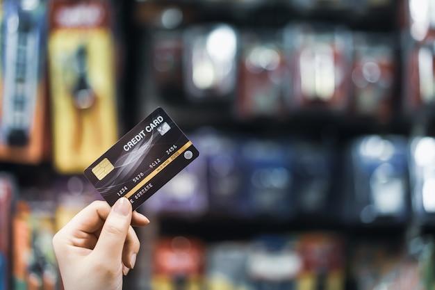 Passi la carta di credito della tenuta con il concetto del supermercato, di acquisto e di vendita al dettaglio della sfuocatura Foto Premium