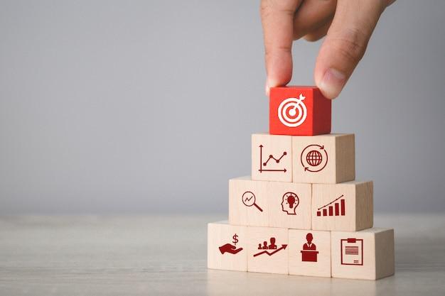 Passi la disposizione del blocco di legno che impila con la freccia e l'affare dell'icona, miranti al concetto di affari. Foto Premium
