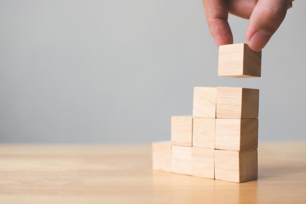 Passi la disposizione del blocco di legno che impila sulla cima con la tavola di legno Foto Premium