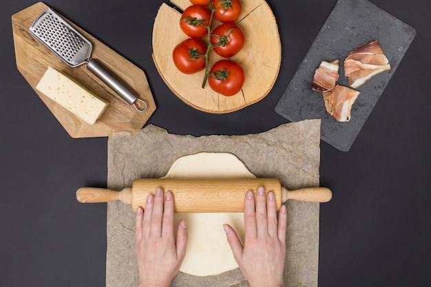 Passi la pasta della pizza di rotolamento sulla carta pergamena con l'ingrediente della pizza su fondo nero Foto Gratuite