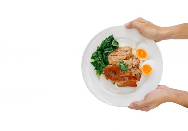 Passi la tenuta della coscia di maiale stufata su riso su fondo bianco. delizioso cibo di strada, cibi ad alto contenuto calorico, fast food che hanno molti grassi. Foto Premium