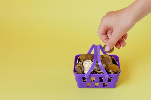 Passi la tenuta della moneta con il mucchio della moneta nel cestino della spesa su giallo Foto Premium