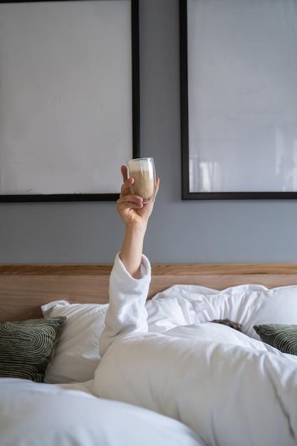 Passi la tenuta della tazza di caffè a casa a letto Foto Gratuite