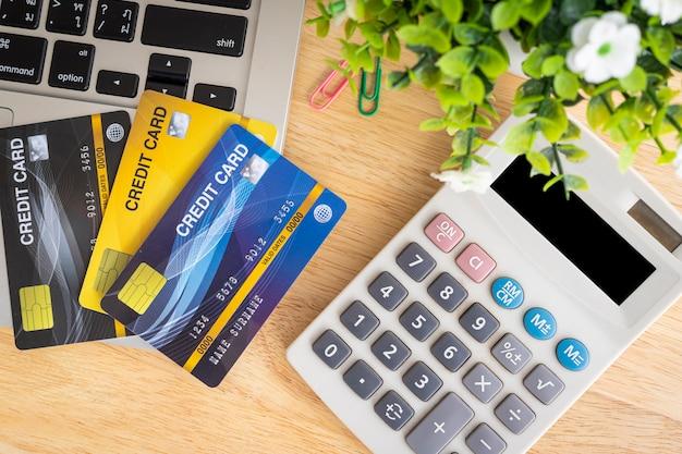 Passi le carte di credito della tenuta con un taccuino e un calcolatore Foto Premium