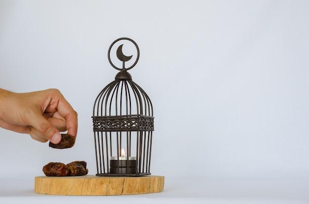 Passi le date della tenuta della frutta della palma con la lanterna che ha il simbolo della luna sulla cima messo sul vassoio di legno su fondo bianco per la festa musulmana del mese santo di ramadan kareem. Foto Premium