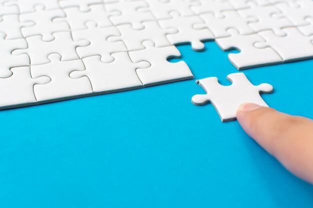 Passi mettere il pezzo di puzzle bianco su fondo blu Foto Premium