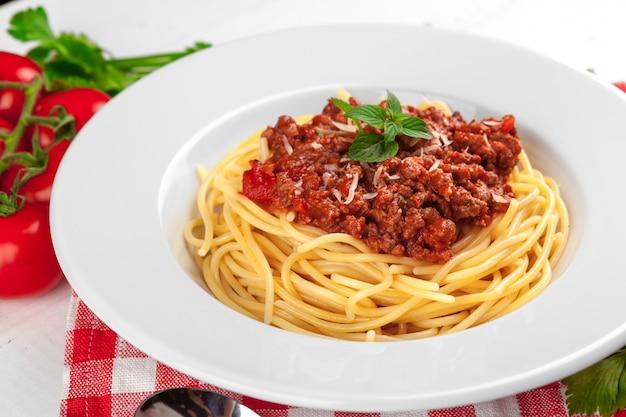 Pasta con carne, salsa di pomodoro e verdure sul tavolo Foto Premium