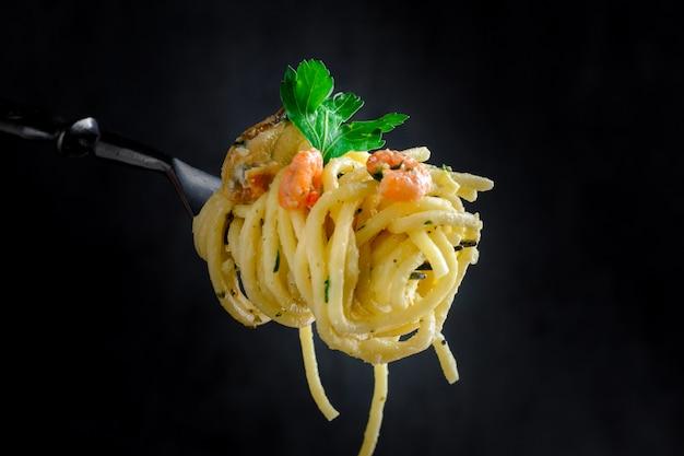 Pasta con cozze e gamberi su una forcella su uno sfondo scuro Foto Premium