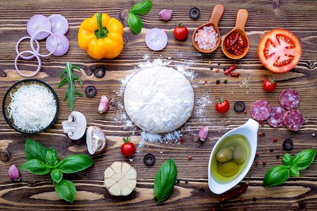 Pasta cruda con ingredienti per pizza fatta in casa Foto Premium