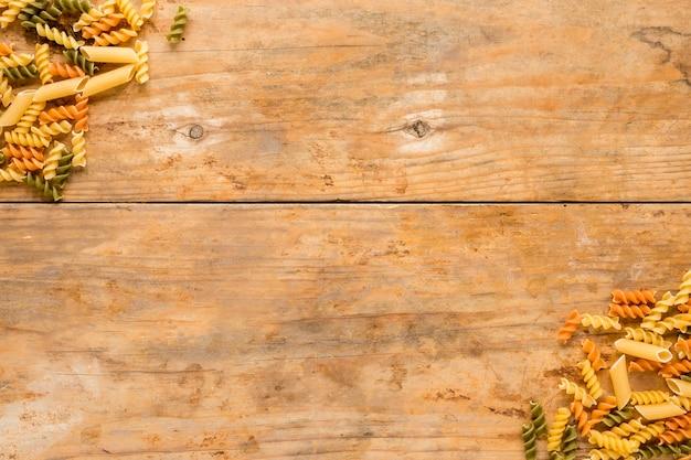 Pasta cruda di fusilli e del penne all'angolo di fondo di legno Foto Gratuite