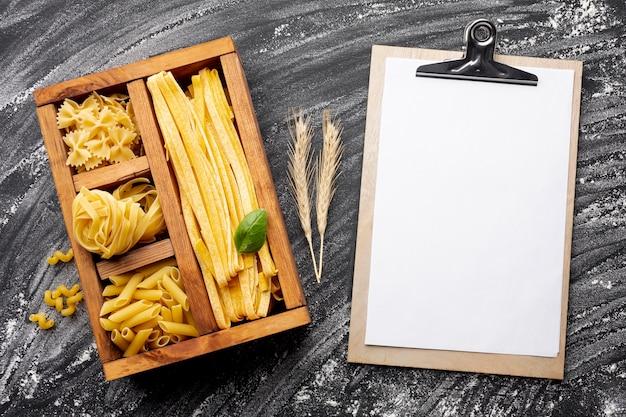 Pasta cruda in scatola di legno con appunti mock-up Foto Gratuite