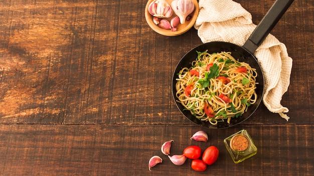 Pasta degli spaghetti con i pomodori e gli spicchi d'aglio sul contesto di legno Foto Gratuite