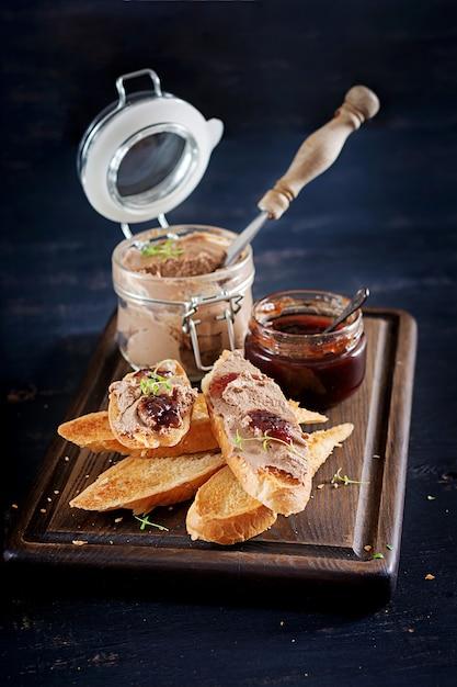 Pasta di fegato di pollo fatta in casa o patè in barattolo di vetro con toast e marmellata di mirtilli rossi con peperoncino. Foto Premium