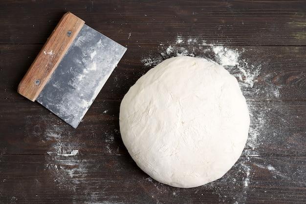 Pasta di lievito appena preparata per pane casereccio di salute su un fondo di legno marrone scuro. Foto Premium