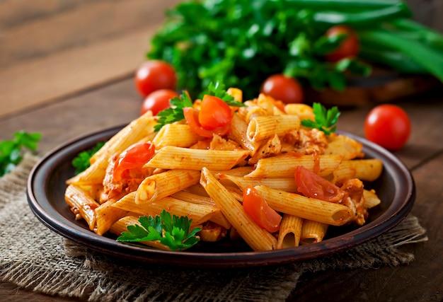 Pasta di penne in salsa di pomodoro con pollo e pomodori su un tavolo di legno Foto Gratuite
