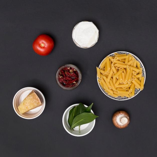 Pasta e ingrediente di penne crude disposte sul bancone della cucina Foto Gratuite