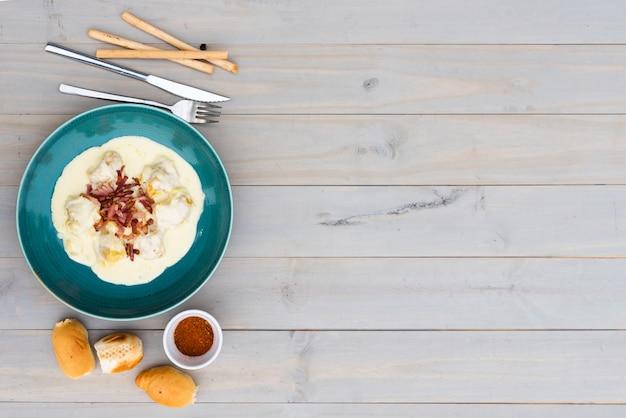 Pasta italiana saporita cremosa in piatto ceramico con pane per il pasto su fondo di legno Foto Gratuite