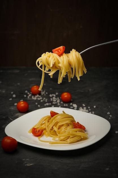 Pasta italiana su un piatto su un buio con pomodorini Foto Premium