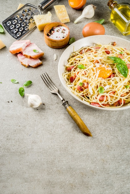 Pasta italiana tradizionale, spaghetti alla carbonara con pancetta, salsa cremosa, parmigiano, tuorlo d'uovo e basilico fresco Foto Premium