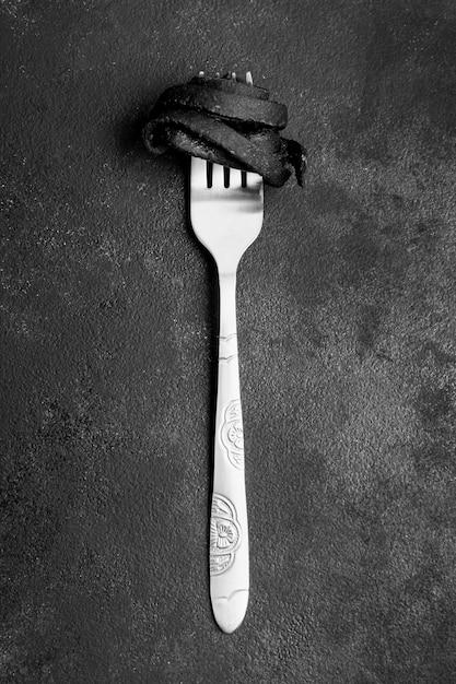 Pasta nera di gamberi avvolta su una forchetta Foto Gratuite