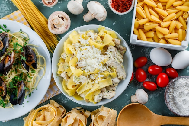 Pasti di pasta in piatti con pasta cruda, pomodoro, farina, funghi, uova, spezie, cucchiaio Foto Gratuite