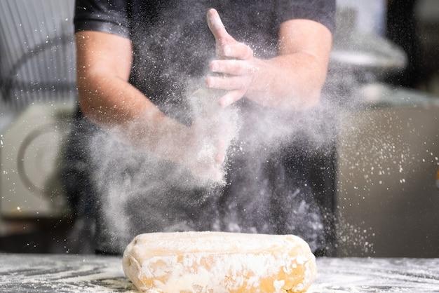 Pasticcere che applaude le sue mani con farina mentre produce la pasta Foto Premium