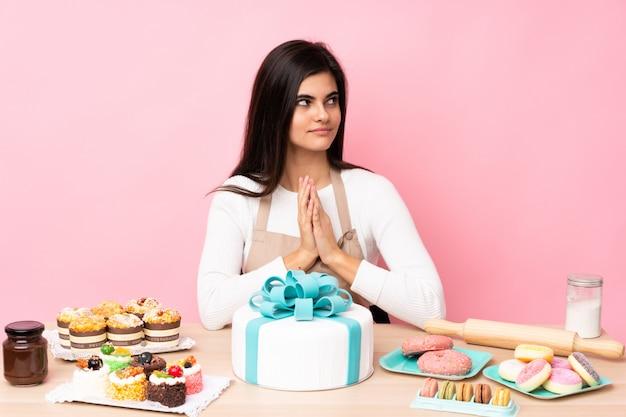 Pasticcere con una grande torta in una tabella sopra la parete rosa che traccia qualcosa Foto Premium
