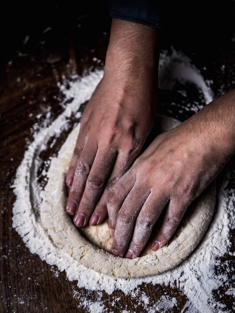 Pasticcere impastare a mano pasta cruda con spolverata di farina bianca sul tavolo della cucina. Foto Premium