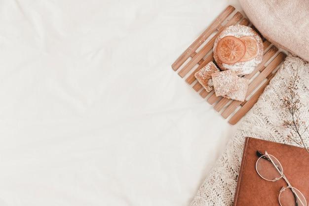 Pasticceria, occhiali da vista, libro e plaid sdraiati sul lenzuolo bianco Foto Gratuite