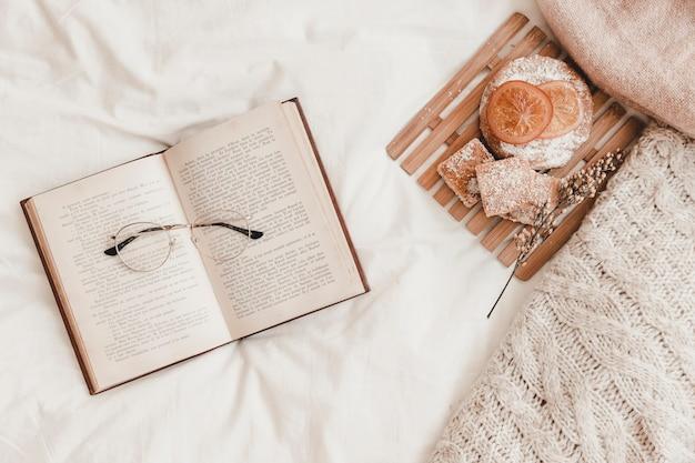 Pasticceria, occhiali da vista sdraiato sul libro aperto sul letto Foto Gratuite