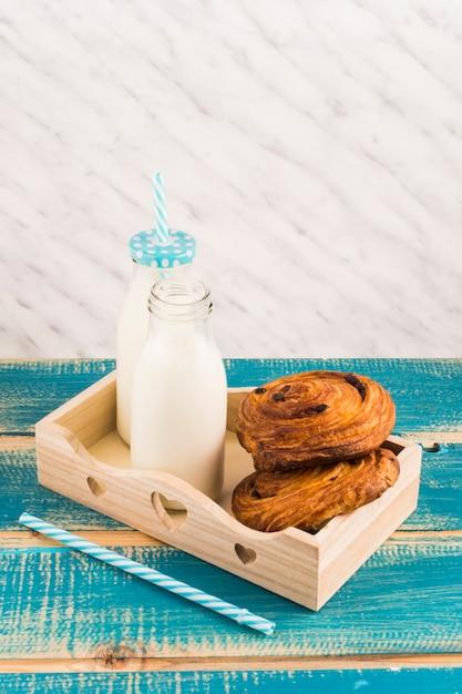 Pasticcerie danesi con la bottiglia per il latte sul vassoio di legno vicino alla paglia sopra la tavola di legno blu Foto Gratuite