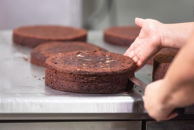 Pasticciere professionista che prepara una deliziosa torta in pasticceria. Foto Premium